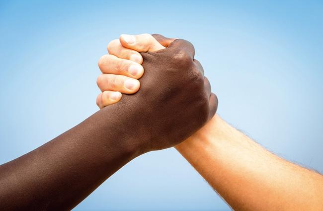 Mãos de uma pessoa negra e outra pessoa branca unidas