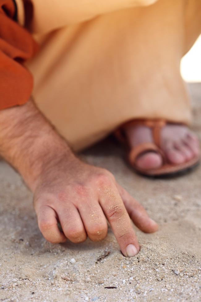 Homem com roupas dos tempos bíblicos escrevendo na areia