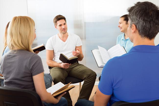 Grupo de pessoas reunidas com bíblias nas mãos