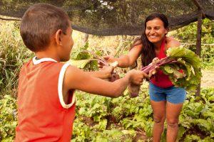Agricultora trocando alimentos com uma criança