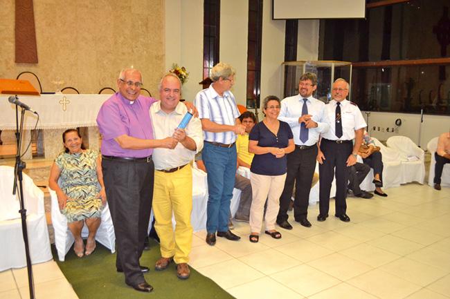 """Bispo Paulo Ayres (à esquerda) entrega """"bastão"""" para o Rev. Sérgio Andrade. Pastora Joana D´arc Meireles assume como 1° tesoureira."""